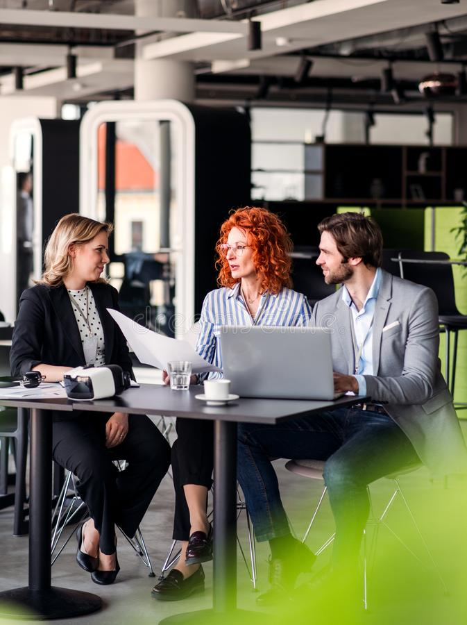 A group of young business people with laptop sitting in an office, talking. royalty free stock photography