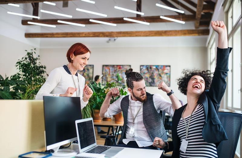Group of young cheerful businesspeople using laptop in office, expressing excitement. stock photo