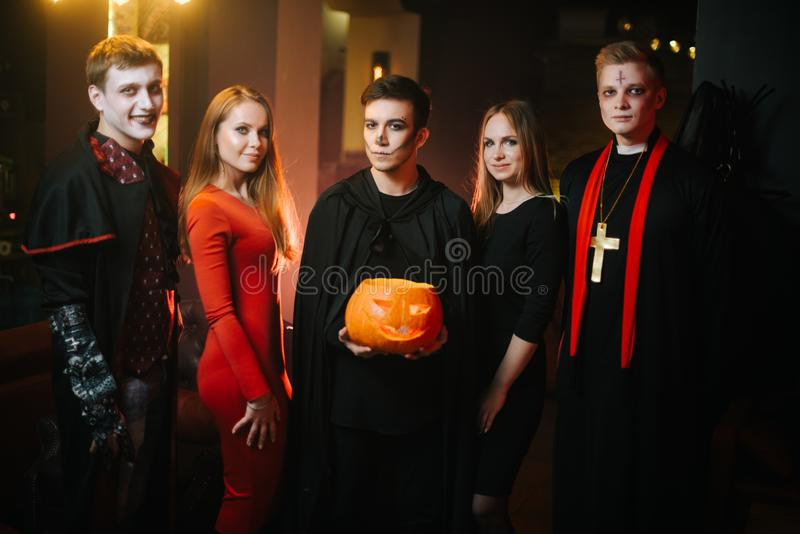 Group of young cheerful friends in colorful costumes is celebrating Halloween royalty free stock image