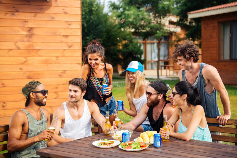 Group of young cheerful friends having fun at picnic outdoors royalty free stock photo