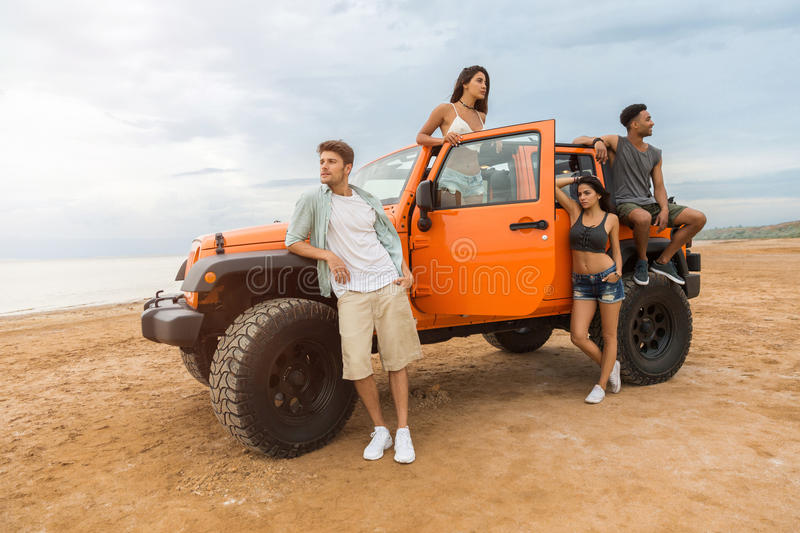 Group of young cheerful people standing near their car. And posing at the beach royalty free stock photo
