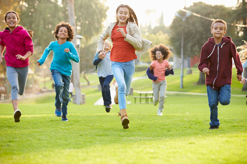 Group Of Young Children Running Towards Camera In Park royalty free stock image