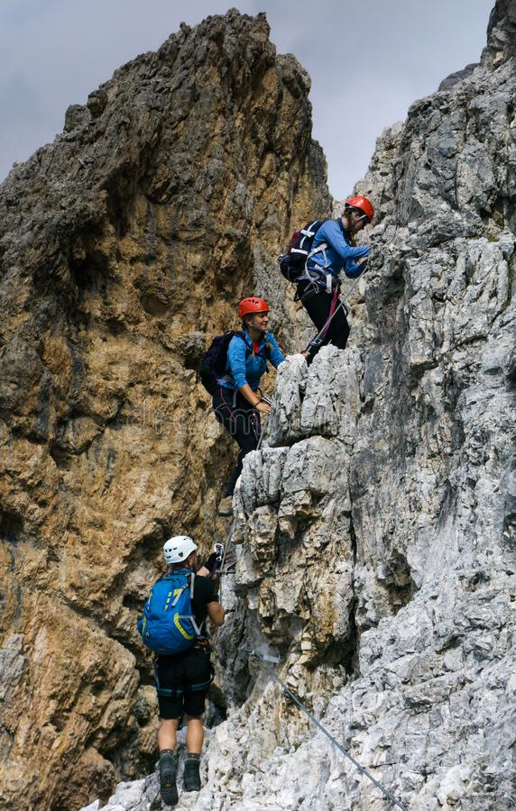 Group of young climbers on a steep vertical Via Ferrata stock images