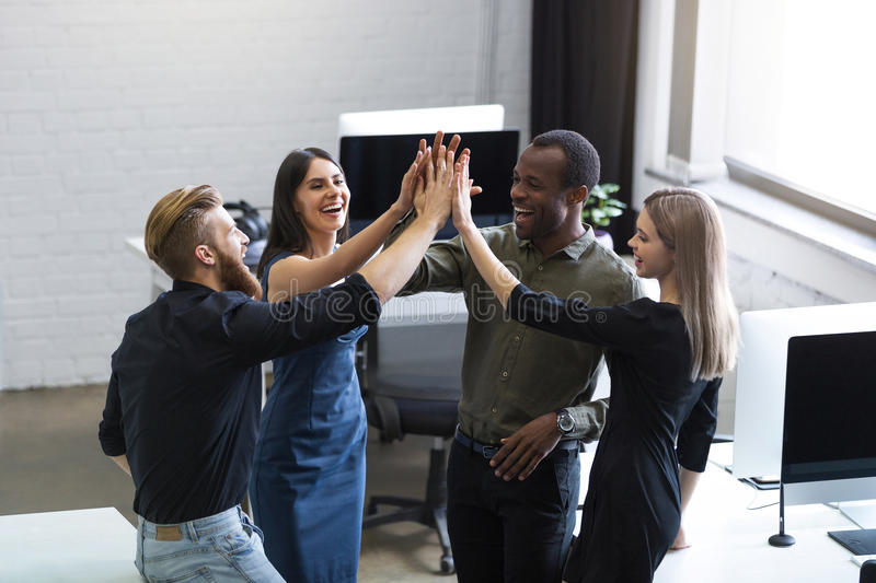 Group of young colleagues giving each other a high five royalty free stock photo