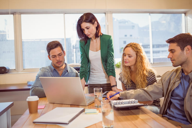 Group of young colleagues using laptop. Group of young colleagues with coffee cups during break at office royalty free stock photography