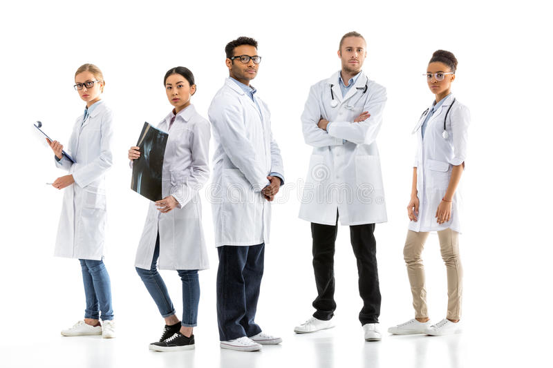 Group of young confident professional doctors in white coats standing stock photo