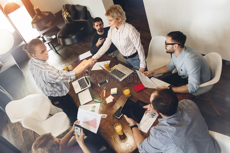 Group of young coworking people meet and make a deal. Man and woman make handshake among business partners. Creative managers sit stock photography