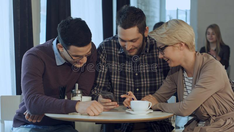 Group of young creative people wearing business casual clothes collaborating at meeting table and discussing work, using. Smartphone. Professional shot in 4K stock photography