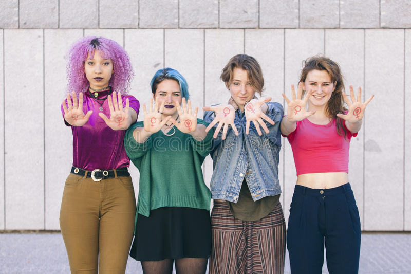 Group of young and diversity women with the symbol of feminism w. Ritten oh their hands and showing them to the front royalty free stock photo