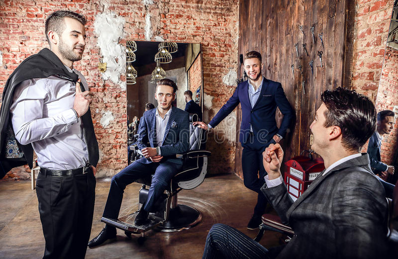 Group of young elegant positive mens pose in interior of barbershop. royalty free stock photo