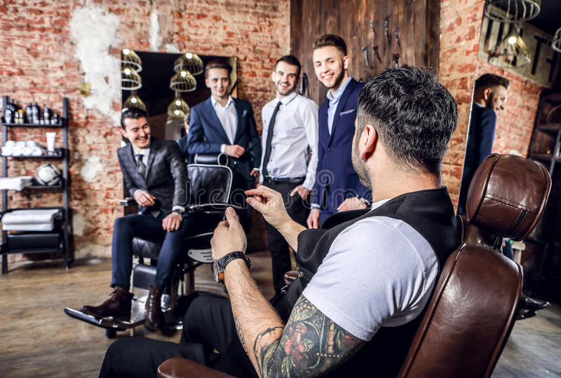 Group of young elegant positive mens pose in interior of barbershop. stock photo