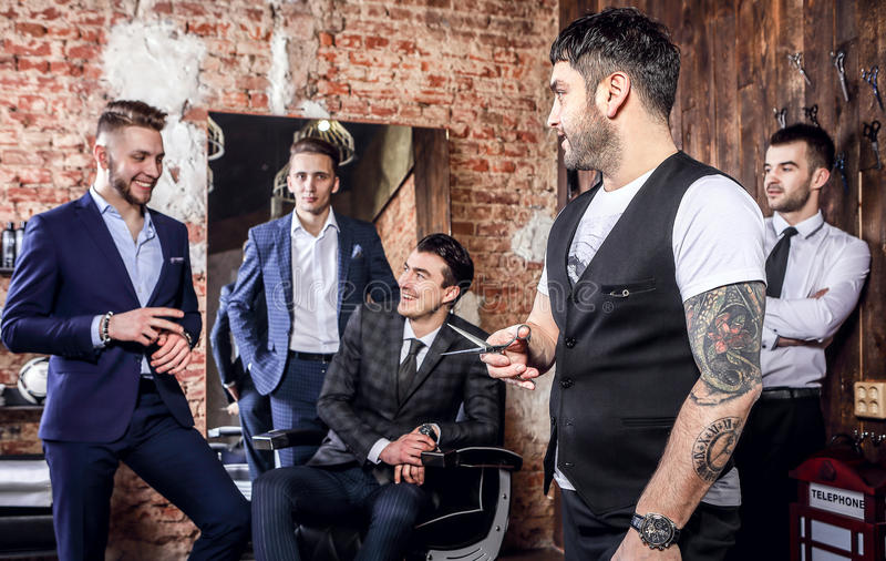 Group of young elegant positive mens pose in interior of barbershop. stock photography