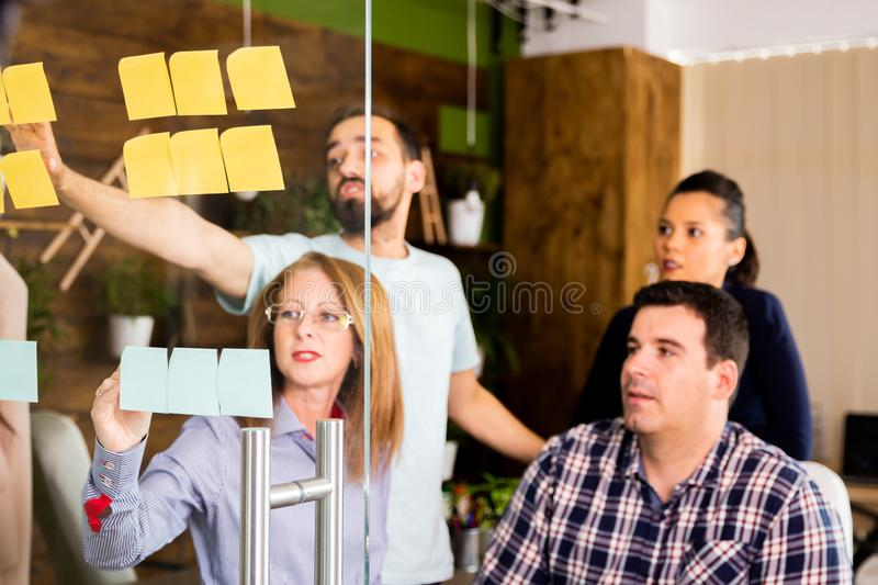 Group of young entrepreneurs looking at sticky notes on a glass window royalty free stock photography