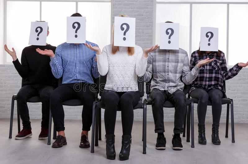 A group of guys and girls, raising their hands questioningly and a paper with a question mark on their faces. A group of young European guys and girls are royalty free stock photo