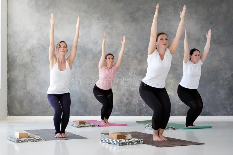 Group of young european woman doung utkatasana or chair pose stock photos