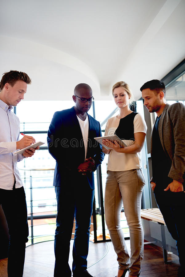 Group of young executives gathered at work. stock photography
