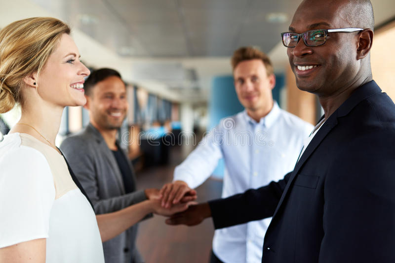 Group of young executives smiling before teamwork. Group of young executives smiling with hands together showing team camaraderie royalty free stock image