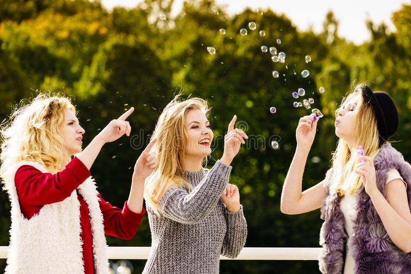 Women blowing soap bubbles, having fun stock images