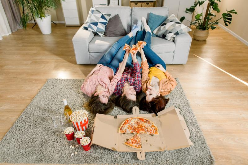 Group of young female friends eating pizza. Three girls eating pizza while lying on the floor with legs on gray sofa royalty free stock photography