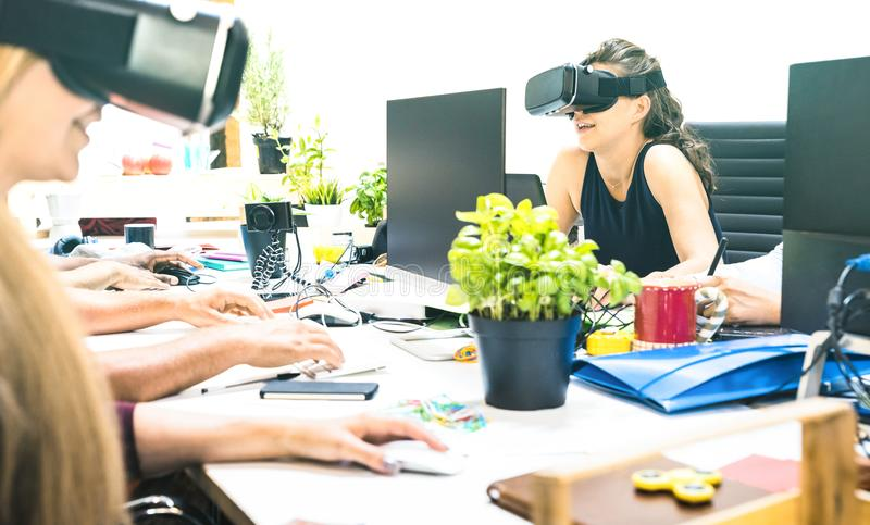 Group of young female people employee workers having fun with vr virtual reality goggles in startup studio - Human resource stock image