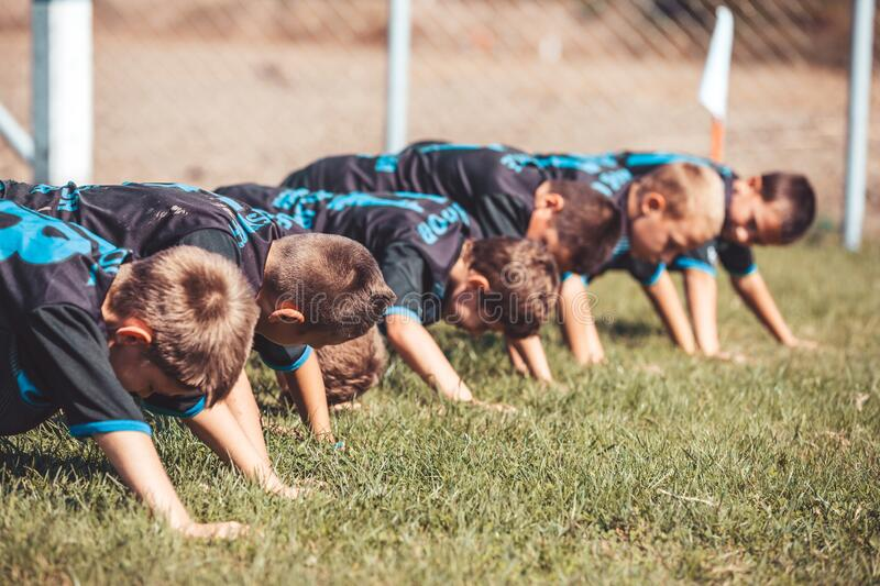 Young players  doing push-up exercises outdoor stock images