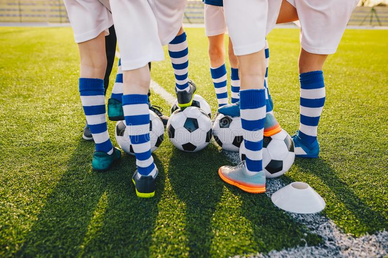 Group of young football players on soccer training. Legs of soccer kids kicking balls on field. Summer sunset in the background. Football training background stock images