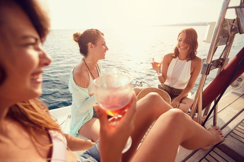 Group of friend's girl having party on sailing boat and drinking wine stock photography