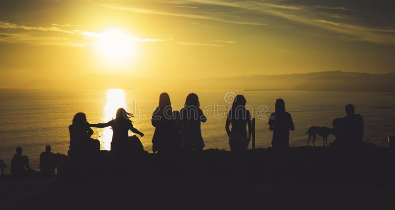 Group of young friends on background beach ocean sunrise, silhouette romantic people dances looking on rear view evening seascape. Happy hipster enjoy sunset stock photo