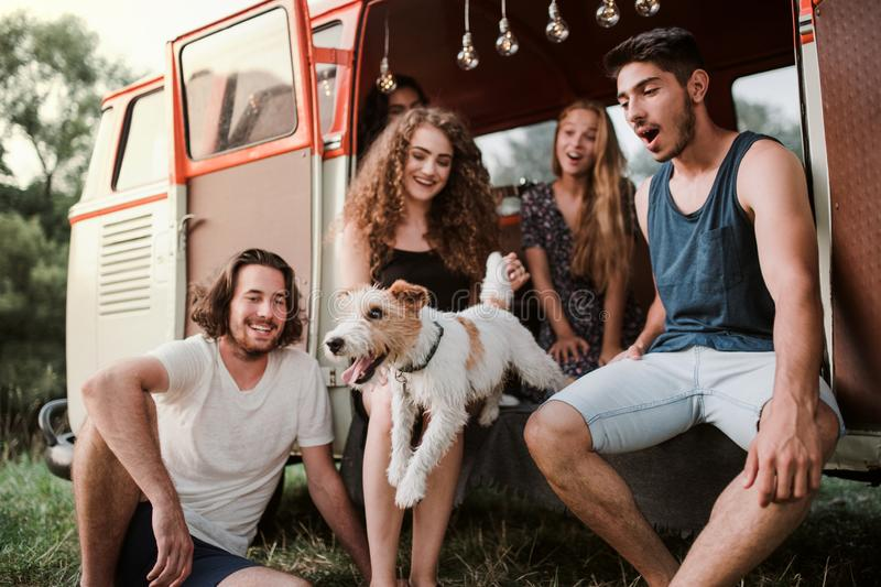 A group of young friends with a dog on a roadtrip through countryside. A group of young friends with a dog by a retro minivan on a roadtrip through countryside stock photography