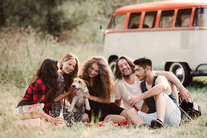 A group of young friends with a dog sitting on grass on a roadtrip through countryside. stock photography