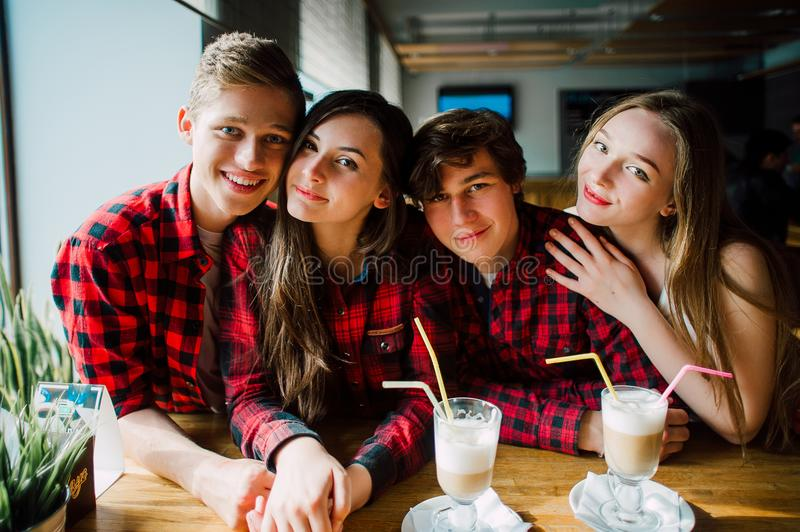 Group of young friends hanging out at a coffee shop. Young men and women meeting in a cafe having fun and drinking coffee. Lifesty stock images