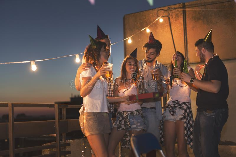 Birthday rooftop party. Group of young friends having a birthday party at a building rooftop, singing a song and blowing a candle royalty free stock images