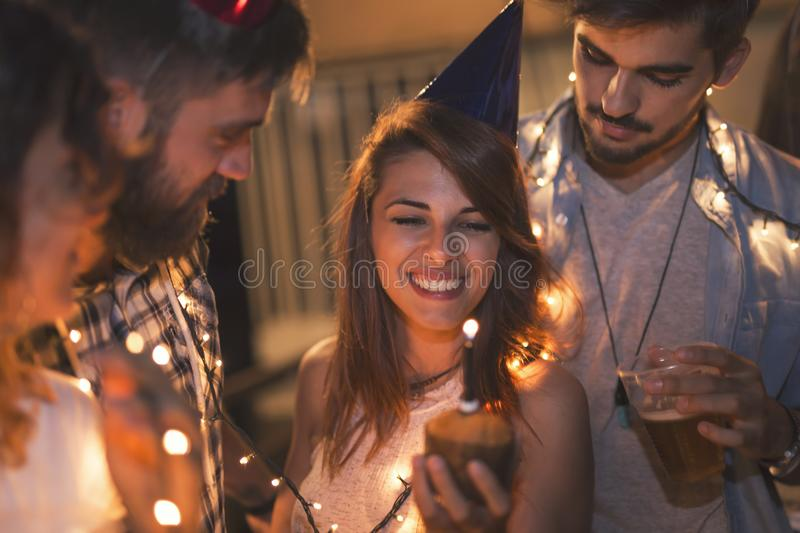Celebrating birthday. Group of young friends having a birthday party at a building rooftop, singing a song and blowing a candle royalty free stock photos