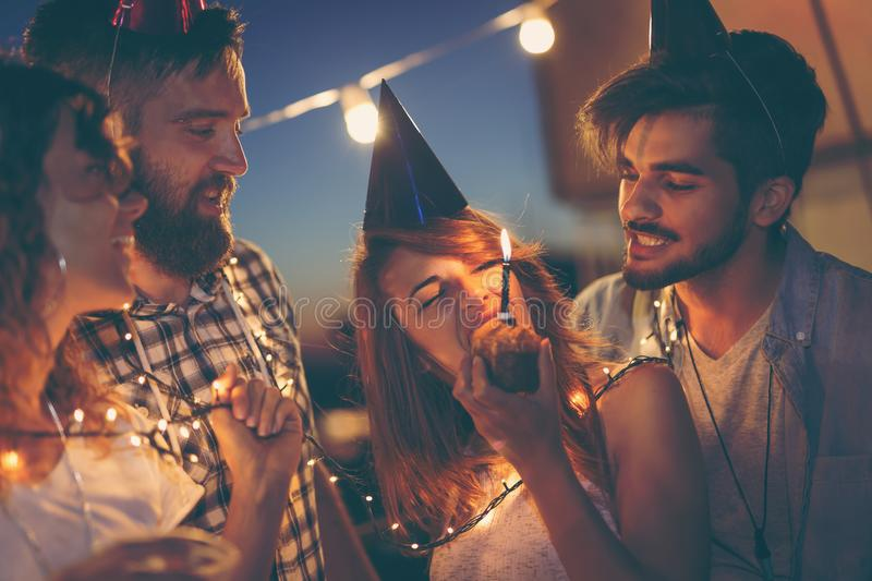 Birthday celebration. Group of young friends having a birthday party at a building rooftop, singing a song and blowing a candle. Focus on a birthday girl eating stock images