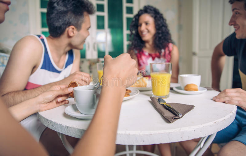 Group of young friends having breakfast at home stock photography