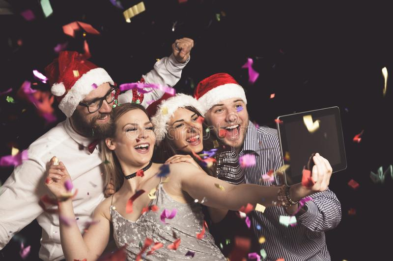 Taking selfies at a party. Group of young friends having fun at New Year`s Eve party and making crazy faces and taking selfies stock photos
