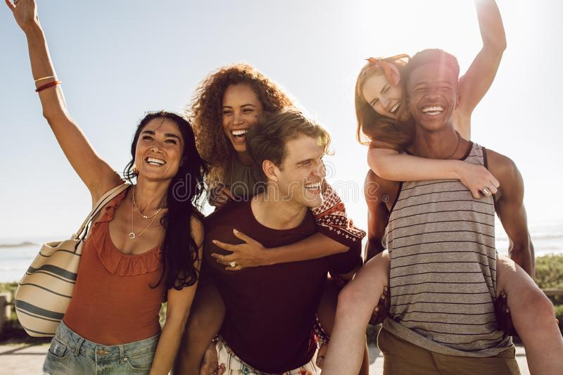 Group of young friends having fun outdoors. Two young men carrying female friends on their back and walking outdoors. Group of young friends having fun outdoors stock images