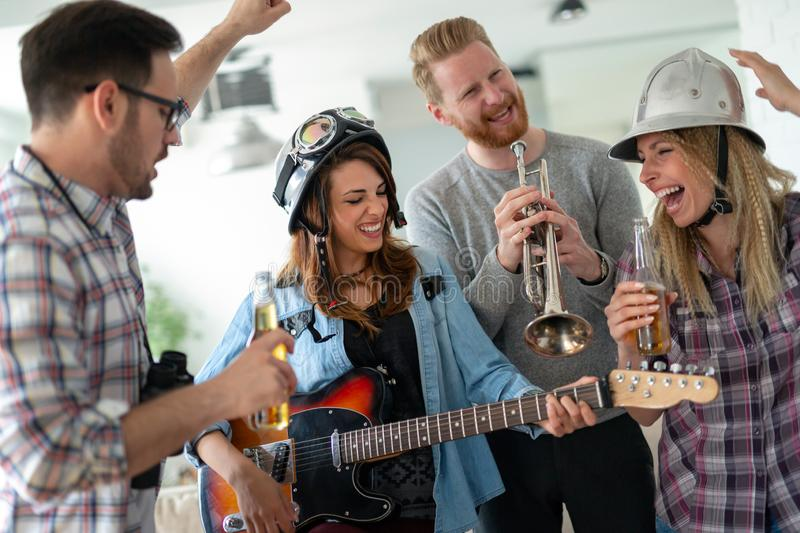 Group of young friends having fun together and playing in music band stock photo