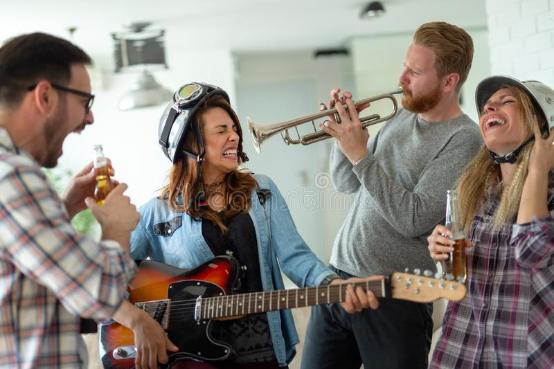 Group of young friends having fun together and playing in music band stock images
