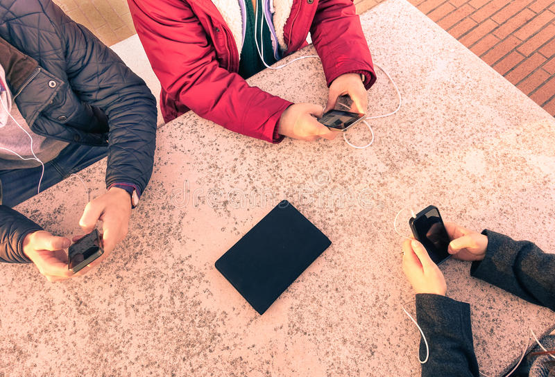 Group of young friends having fun together with smartphone. On marble table - Closeup of mixed hands social networking in urban contest - Technology and royalty free stock photos