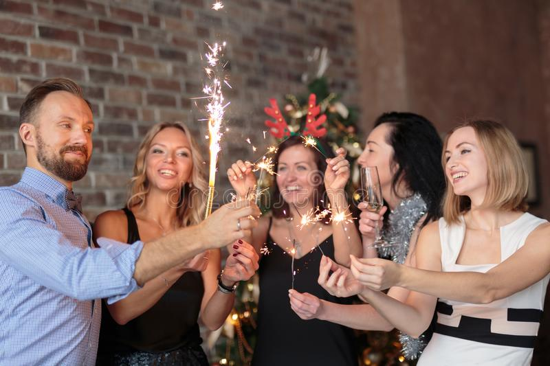 Group of young friends holding sparklers at Christmas party stock image
