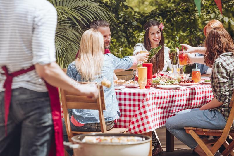 A group of young friends making a toast while sitting by a table. Full of food during a grill party outside concept stock images