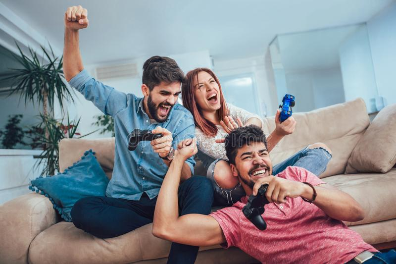Young friends play video games together at home. Group of young friends play video games together at home royalty free stock photos