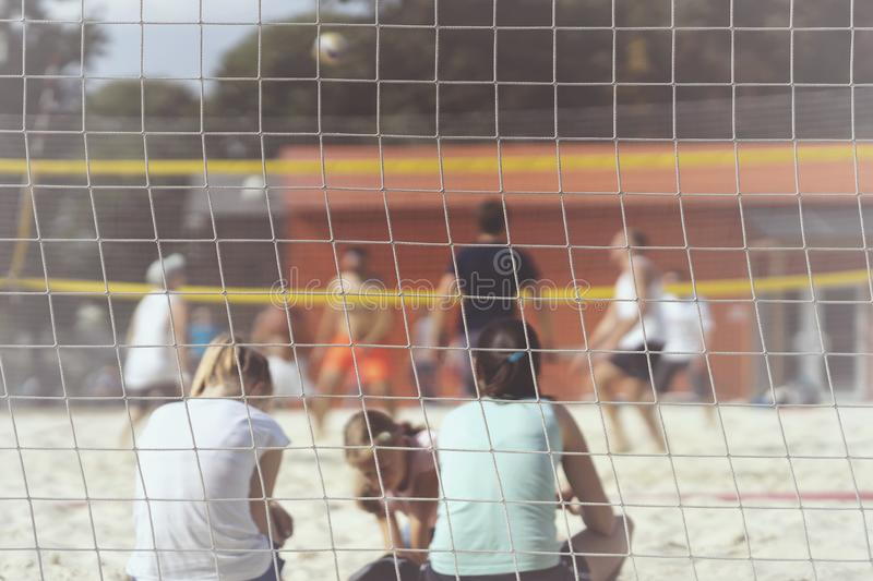 Group of young friends playing beach volleyball, unrecognizable girl fans back to us, summer day, selectiv focus stock photo