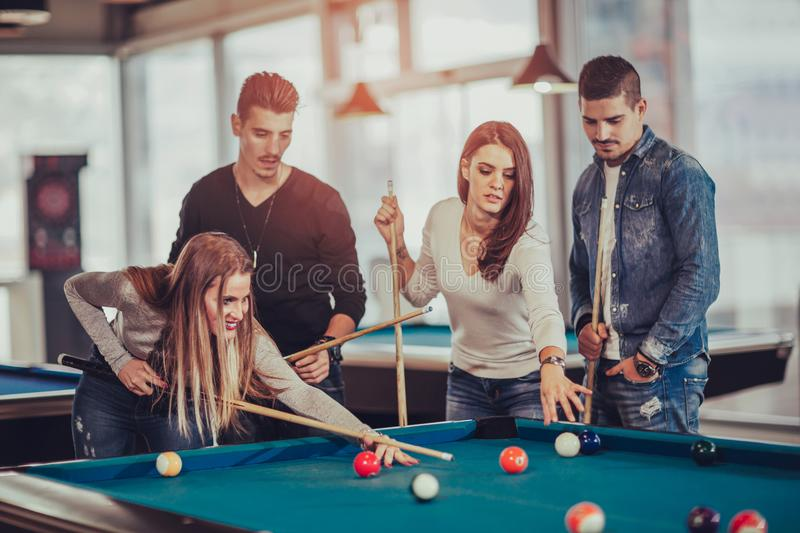 Group of young friends playing billiard royalty free stock image