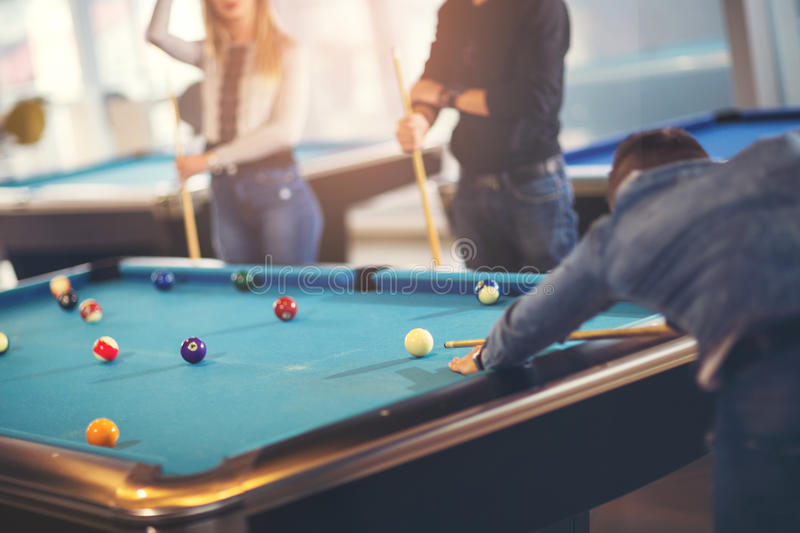 Group of young friends playing billiard. In cafe royalty free stock photos