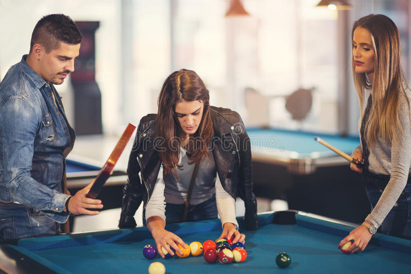 Group of young friends playing billiard. In cafe stock photo