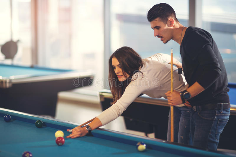 Group of young friends playing billiard. In cafe royalty free stock images