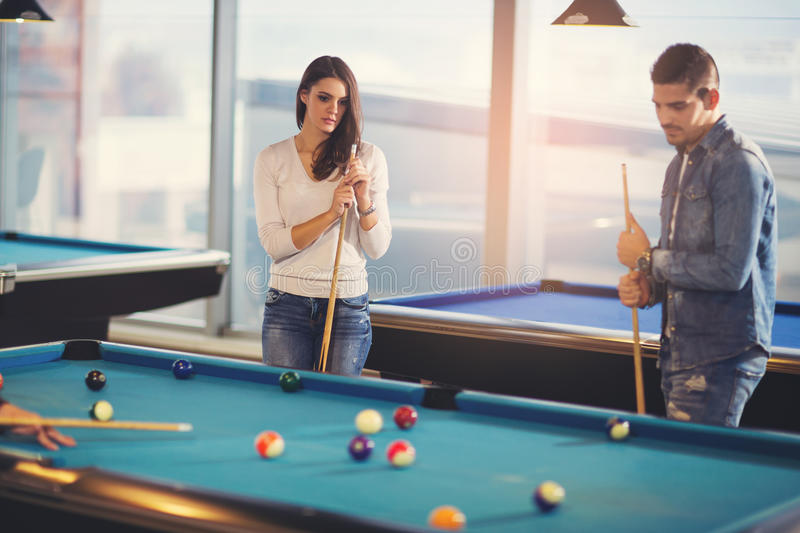 Group of young friends playing billiard. In cafe stock photography