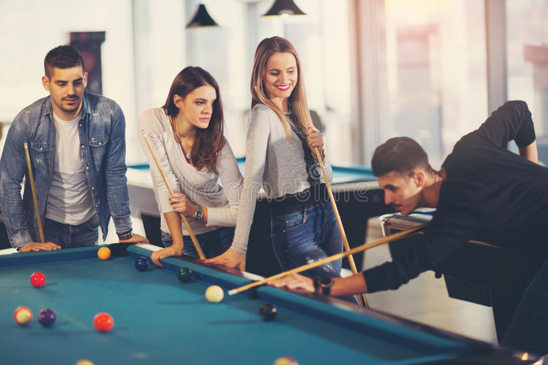 Group of young friends playing billiard. In cafe royalty free stock photo